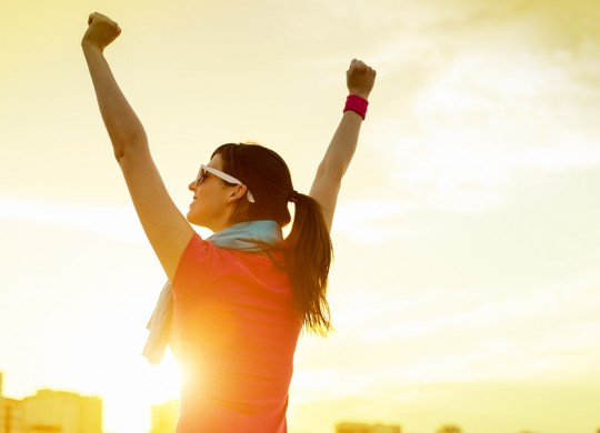 Sportswoman with arms up celebrating success
