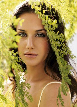 Frau, Gesicht geschminkt, gelbe Tunika, zwischen Pflanzen